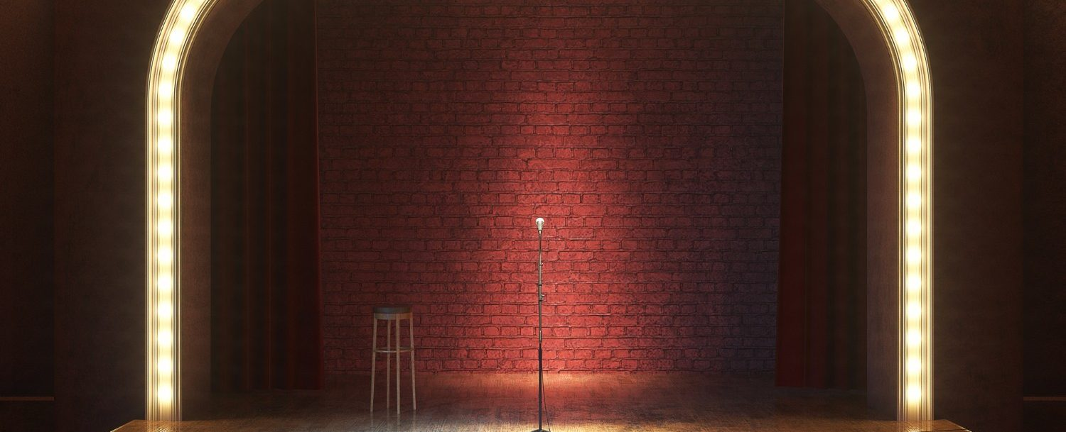 Theaters in Buffalo | Visit one of the best Theaters in Buffalo! | Standing mic in the middle of a small stage spotlit