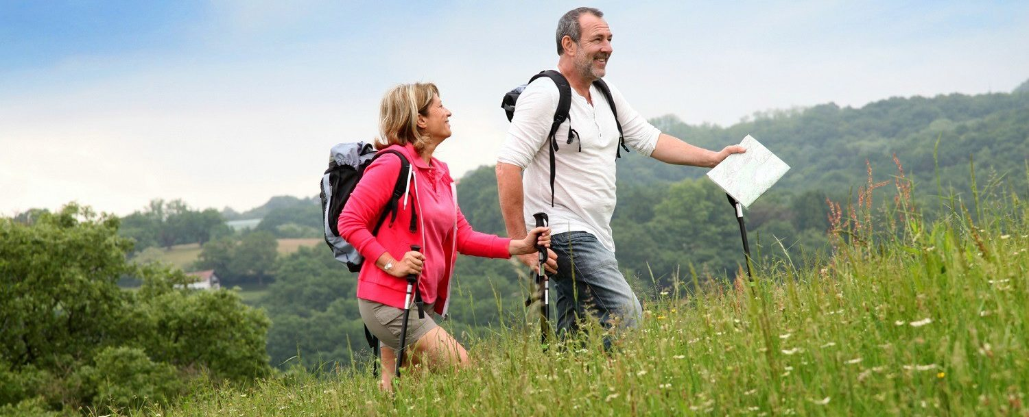 Enjoy these Western New York Attractions | Couple hiking on a hilly meadow